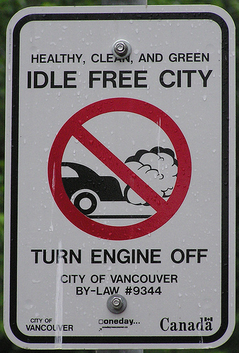 A sign stating it is law to not allow your car motor to idle while stopped